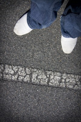 11591371-white-shoes-of-a-pedestrian-about-to-step-over-a-road-line-marking-to-get-to-the-other-side-of-the-s