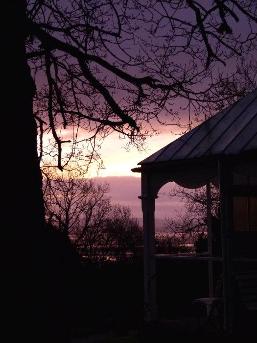 summerhouse silhouetted against a dawn sky