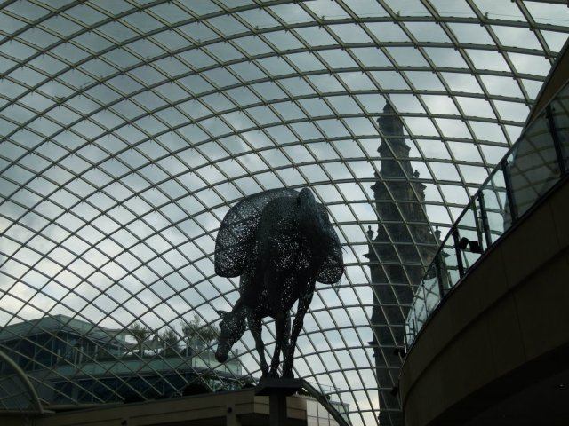 Cityscape of panelled glass roof, with sculpture made of fragments, modern penthouse and old church