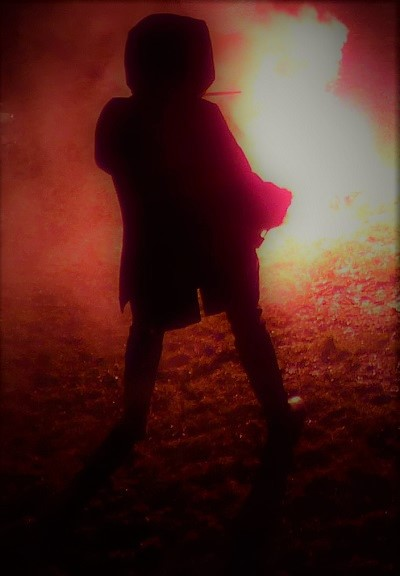 hooded figure in front of a bonfire, possibly holding a wand