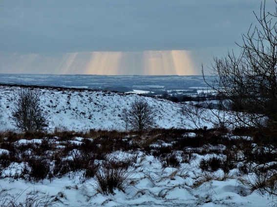 snowy moorland landscape from a high viewpoint, shafts of light breaking through thick cloud