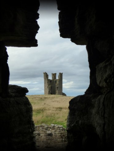 picture of a keep on a bare hill, seen through the cross shaped window of another castle or keep